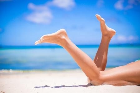Photo pour Female beautiful smooth legs on white sand beach - image libre de droit