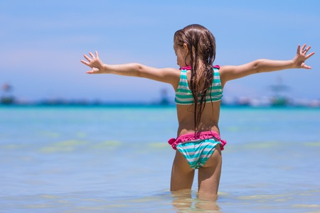 Photo for Happy little girl having fun, swimming and jumping at shallow water - Royalty Free Image