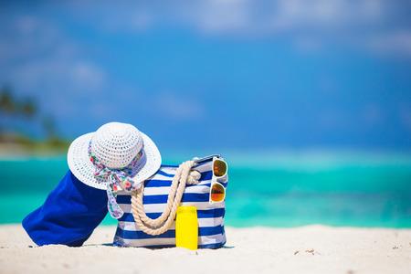 Foto de Blue stripe bag and towel, straw white hat, sunglasses, sunscreen bottle on exotic beach - Imagen libre de derechos