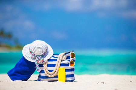 Photo pour Blue stripe bag and towel, straw white hat, sunglasses, sunscreen bottle on exotic beach - image libre de droit