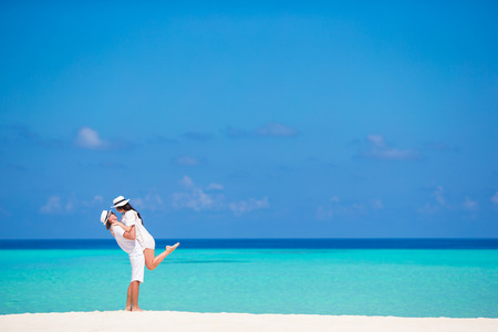 Foto de Young happy couple on white beach at summer vacation - Imagen libre de derechos