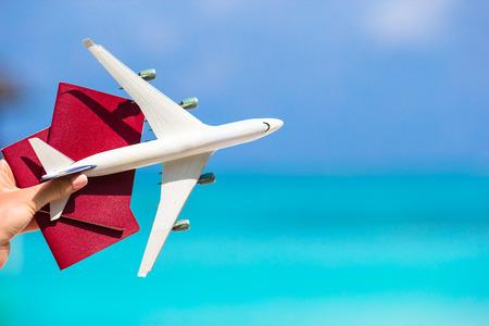 Foto de Closeup of passports and white airplane background the sea - Imagen libre de derechos