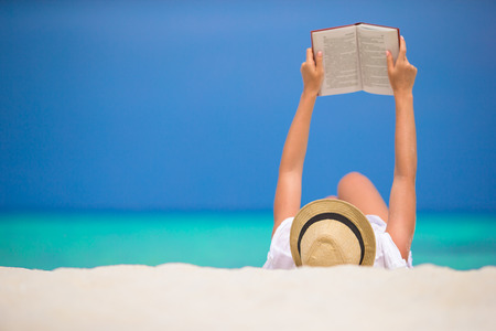 Photo pour Young woman is reading on tropical white beach - image libre de droit
