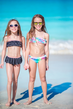 Photo pour Adorable little girls have a lot of fun on the beach. Two beautiful kids are happy - image libre de droit
