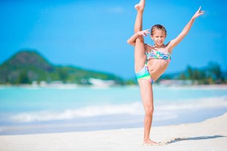 Foto de Beautiful little girl on beach having fun. Happy girl enjoy summer vacation background the blue sky and turquoise water in the sea on caribbean island - Imagen libre de derechos