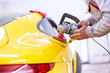 Foto de Polishing the yellow machine for customer service. - Imagen libre de derechos