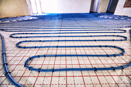 Photo pour Laying blue pipes for floor heating at the construction site. - image libre de droit