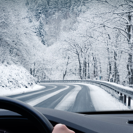 Photo pour Winter Driving - Winter country road leading through a mountain landscape. - image libre de droit