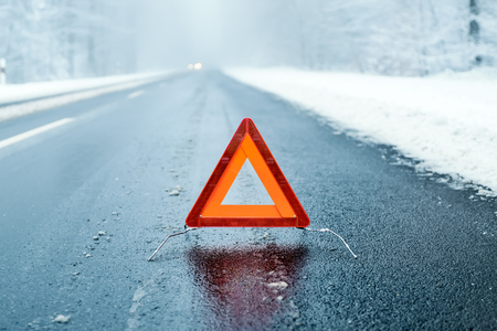 Foto de Winter Driving - Warning triangle on a winter road - Imagen libre de derechos