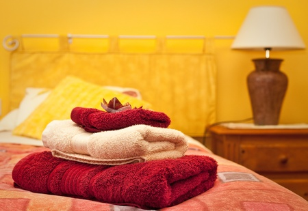 Photo for A pile of towels on a bed in a hotel room - Royalty Free Image
