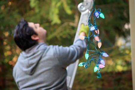 Foto de young man in gray climbing a ladder to decorate for christmas - Imagen libre de derechos