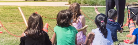 Panorama rear view of diverse kids sitting on grass lawn attending outdoor summer game in Texas, America