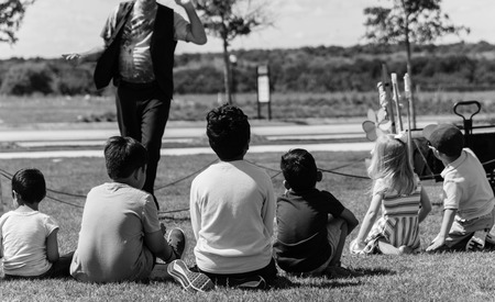 Vintage tone rear view of diverse kids sitting on grass lawn attending outdoor summer game in Texas, America