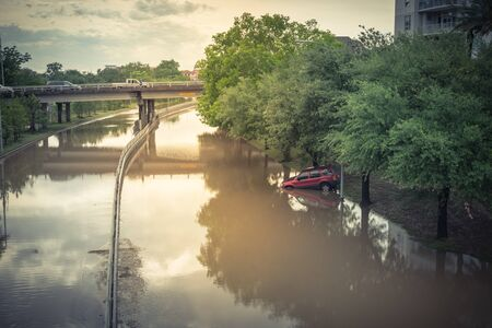 Photo for Swamped car by flood water near downtown Houston, Texas, USA. Flooded car under deep water on a heavy high water road. Disaster Motor Vehicle Insurance Claim Themed. Severe weather concept - Royalty Free Image