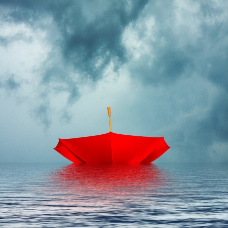 Upside down bright red umbrella floating on water background in stormy weather
