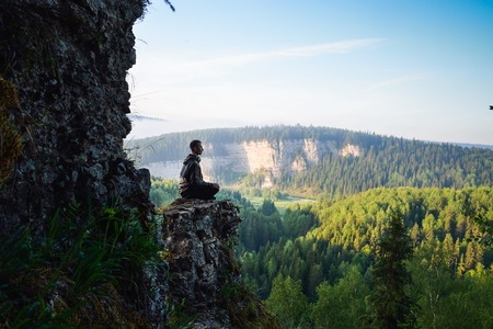 Photo pour Man sitting on the top of the mountain in yoga pose, leisure in harmony with nature. - image libre de droit