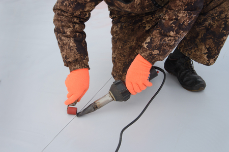 Foto de Waterproofing and insulation at construction site, roof sealing process of synthetic membrane with Hot Air Hand Tool. New protection technology. Closeup. - Imagen libre de derechos