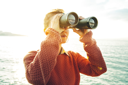Foto de Beautiful Young Girl Looking Through Binoculars At The Sea On A Bright Sunny Day. Wanderlust Journey Concept - Imagen libre de derechos