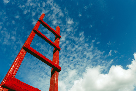 Foto de Red Staircase Rests Against Blue Sky. Development Motivation Business Career Growth Concept - Imagen libre de derechos