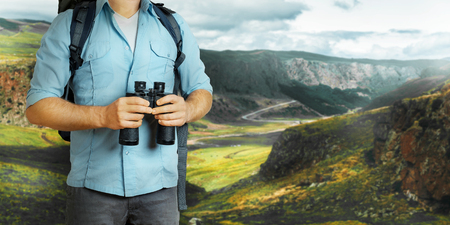 Photo for Young Traveler Man With Backpack And Binoculars Seeking Direction. Hiking Tourism Journey Concept - Royalty Free Image