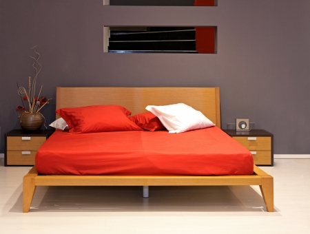 Minimalistic double bed in modern bedroom interior