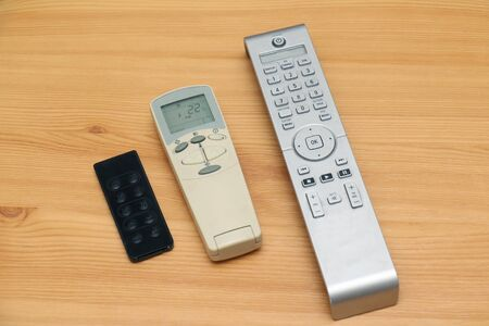 Photo for Remote controls for house appliances on wooden table - Royalty Free Image