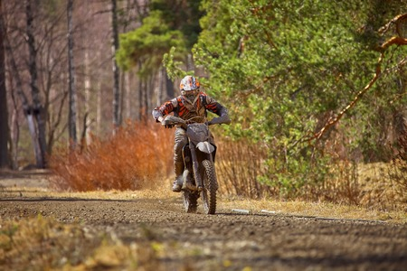 Motocross driver on muddy offroad track and wet terrain at cross country competition in Parola, Finland.