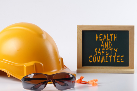 Foto de Yellow hardhat safety helmet,safety glass and ear plug isolated on white background with HEALTH AND SAFETY  COMMITTEE words. Industrial safety and health conceptual. - Imagen libre de derechos