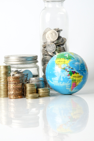 Foto de Global economy concept with sphere globe and stacked of coins over white. - Imagen libre de derechos