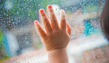 Rain drops on the car window and children hand . Abstract background