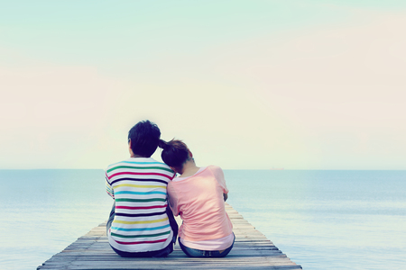 Photo for Two lovers sitting on the bridge at the sea. - Royalty Free Image