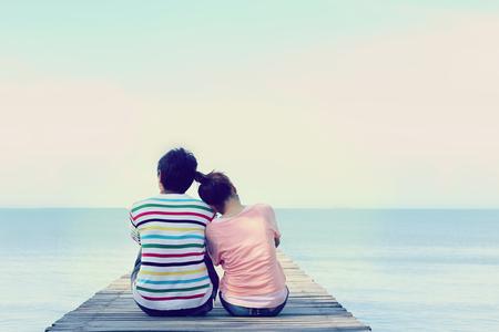 Foto de Two lovers sitting on the bridge at the sea. - Imagen libre de derechos