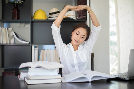 Photo for Asian woman stretching at her workplace and smiling in the office - Royalty Free Image