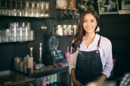 Foto de Asian women Barista smiling and using coffee machine in coffee shop counter - Working woman small business owner food and drink cafe concept - Imagen libre de derechos