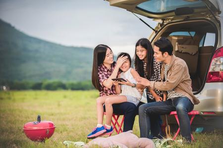 Foto de Happy little girl  with asian family sitting in the car for enjoying road trip and summer vacation in camper van - Imagen libre de derechos