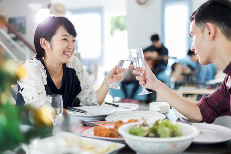 Foto de Asian young couple enjoying a romantic dinner  evening drinks while sitting at the dinning table on the kitchen together - Imagen libre de derechos