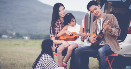 Photo pour happy little girl playing ukulele with asian family sitting in the car for enjoying road trip and summer vacation,soft focus - image libre de droit