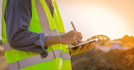 Foto de Asian engineer with hardhat using  tablet pc computer inspecting and working at construction site - Imagen libre de derechos