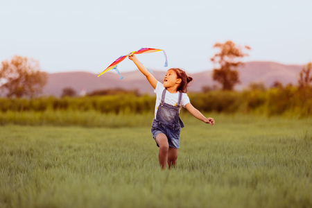 Photo for Asian child girl and father with a kite running and happy on meadow in summer in nature - Royalty Free Image