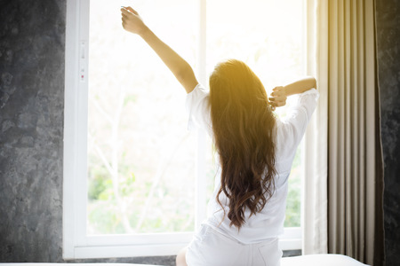 Foto de Asian woman Beautiful young smiling woman sitting on bed and stretching in the morning at bedroom after waking up in her bed fully rested and open the curtains in the morning to get fresh air. - Imagen libre de derechos