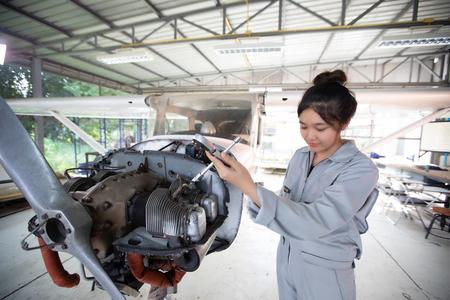 Foto de Asian men and women Engineers and technicians are repairing aircraft. - Imagen libre de derechos