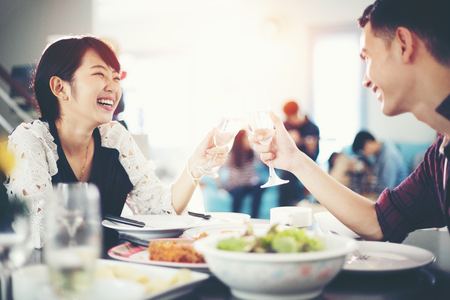 Photo for Asian young couple enjoying a romantic dinner  evening drinks while sitting at the dinning table on the kitchen together,soft focus - Royalty Free Image