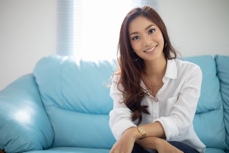 Photo for Asian women smiling happy for relaxation on sofa at home - Royalty Free Image