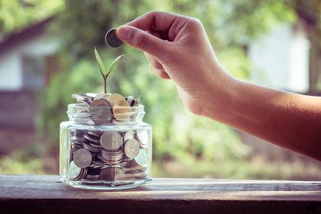 Foto de hand putting money coins  with filter effect retro vintage style - Imagen libre de derechos