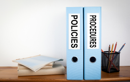Photo pour Policies and Procedures binders in the office. Stationery on a wooden shelf. - image libre de droit