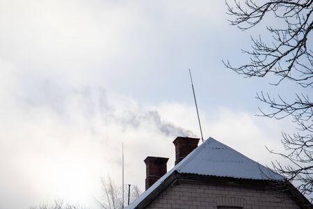 Foto de Dark smoke comes out of a house's chimney, winter day. Pollution, ecology and global warming - Imagen libre de derechos
