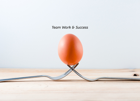 Foto per Egg on the fork with text teamwork business concept - Immagine Royalty Free