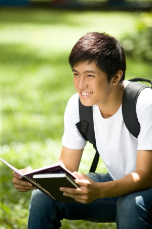 Photo for Young handsome Asian student open book and smile in outdoor - Royalty Free Image