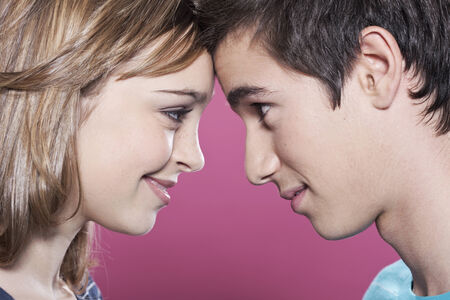 Photo for Attractive teenage girl and boy looking at each other smiling - Royalty Free Image