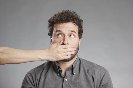 Foto de Woman's hand covering mature man's mouth - Imagen libre de derechos